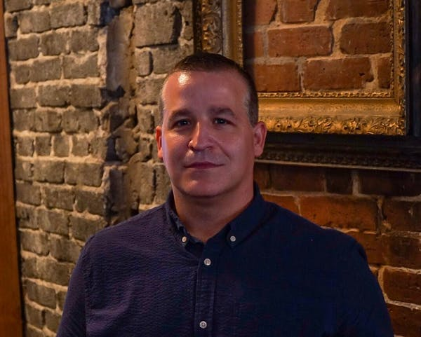 mark standish standing in front of a brick wall posing for the camera