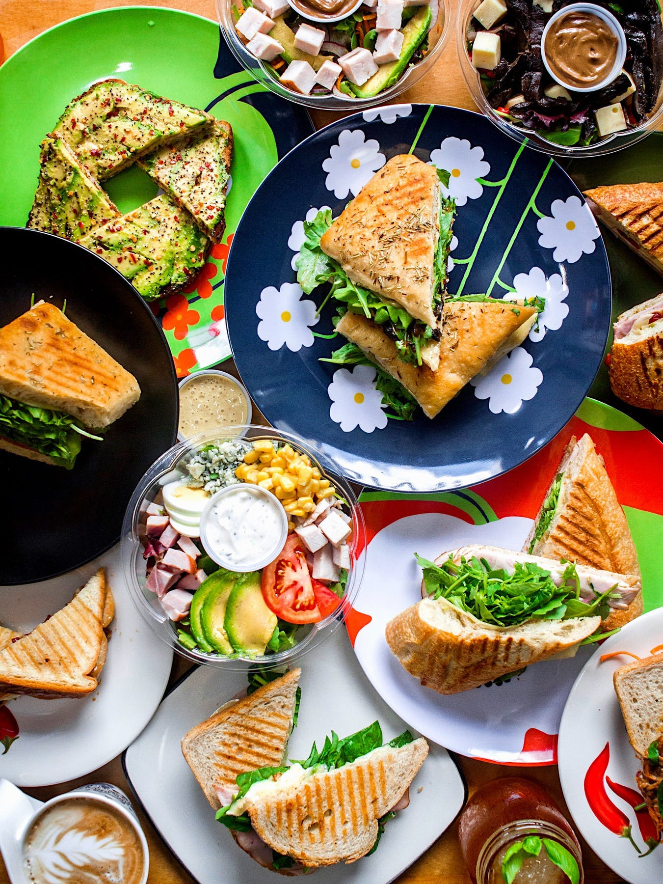 plates of food on a table, most of them sandwiches