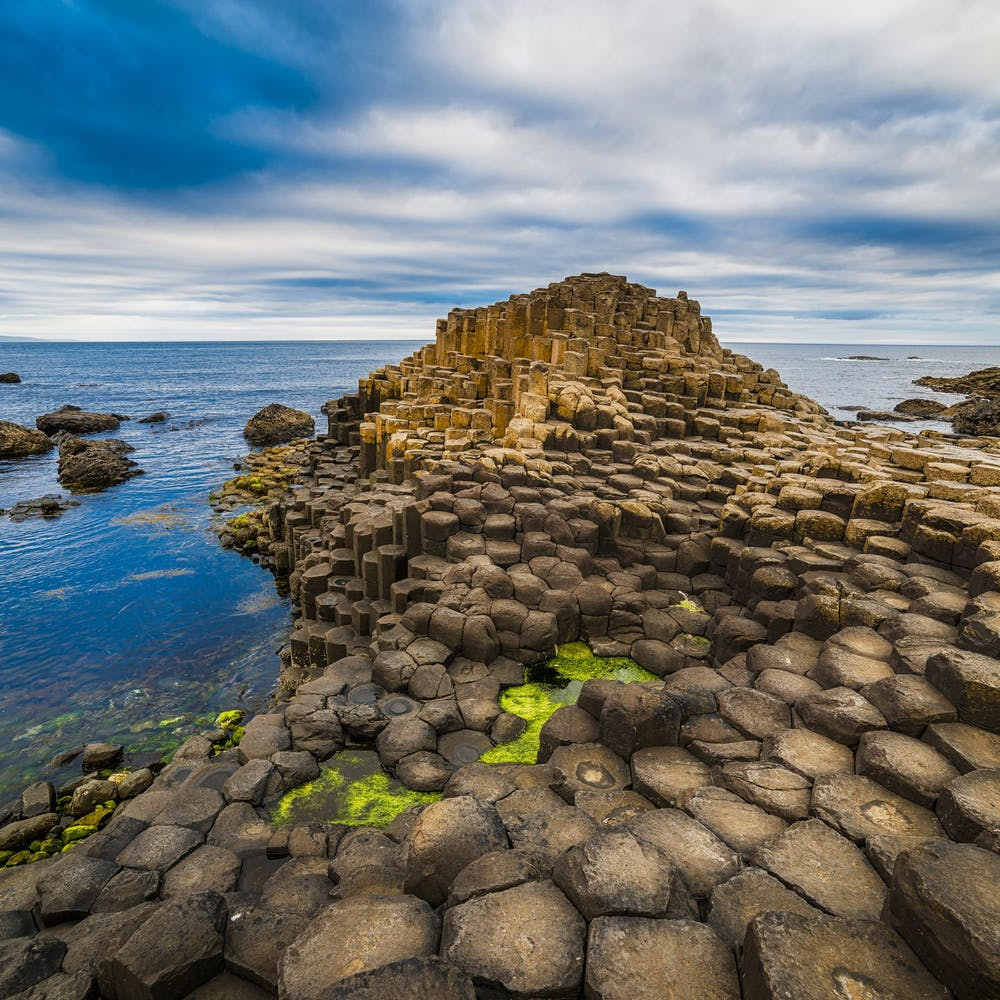 a rocky beach next to a body of water with Giant's Causeway in the background