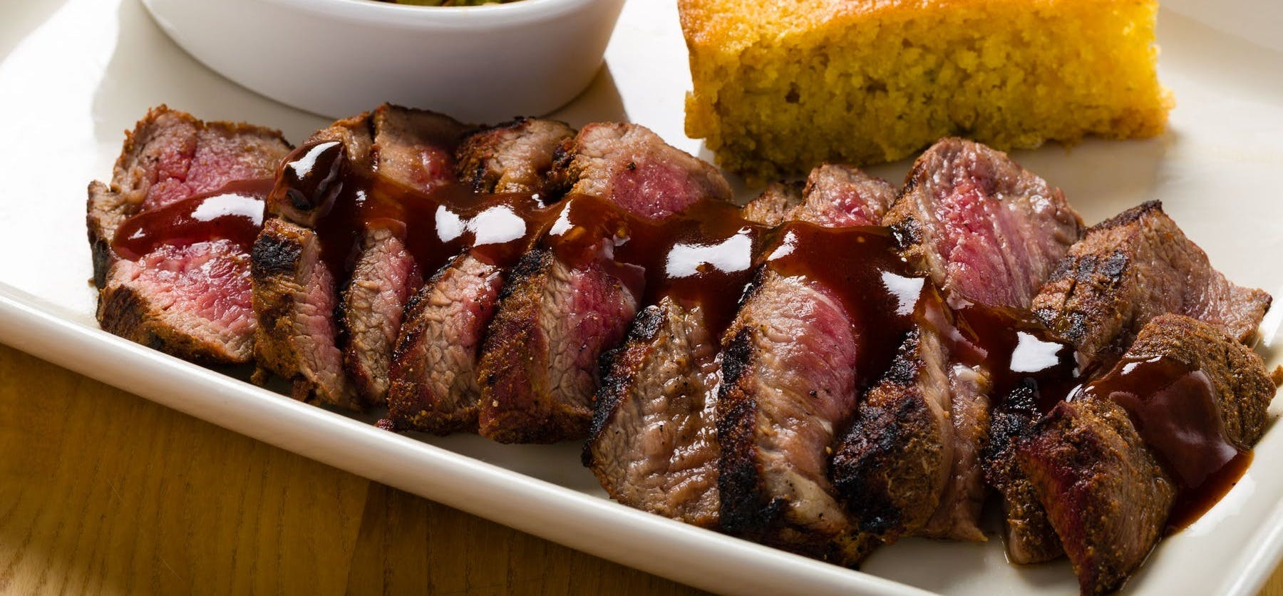 steak slices with barbecue sauce, corn bread and coleslaw
