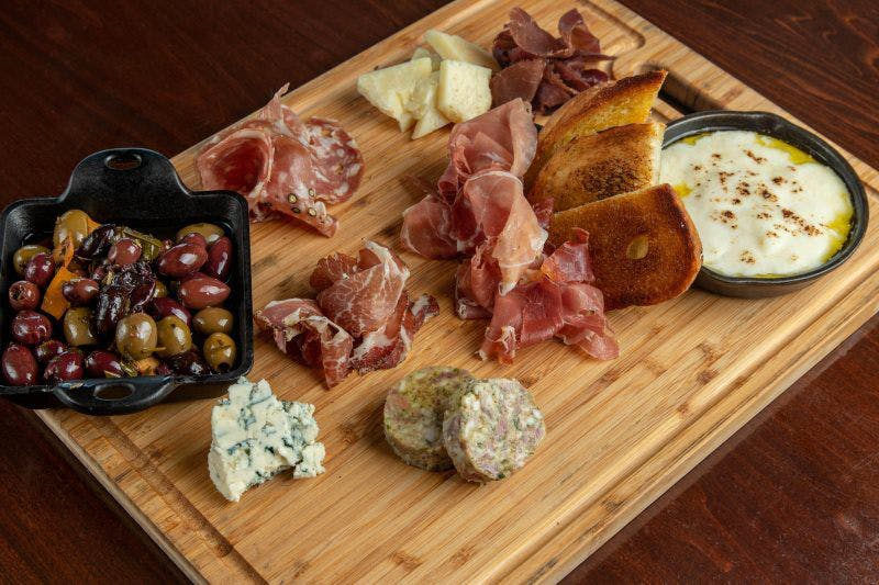 a plate of food sitting on top of a wooden cutting board
