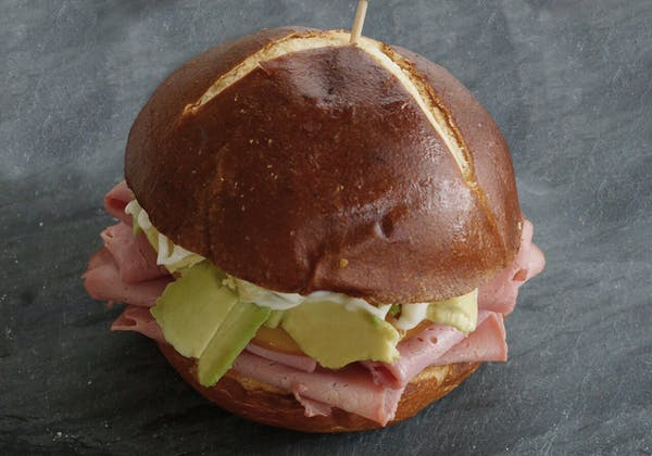 a half eaten sandwich sitting on top of a piece of paper