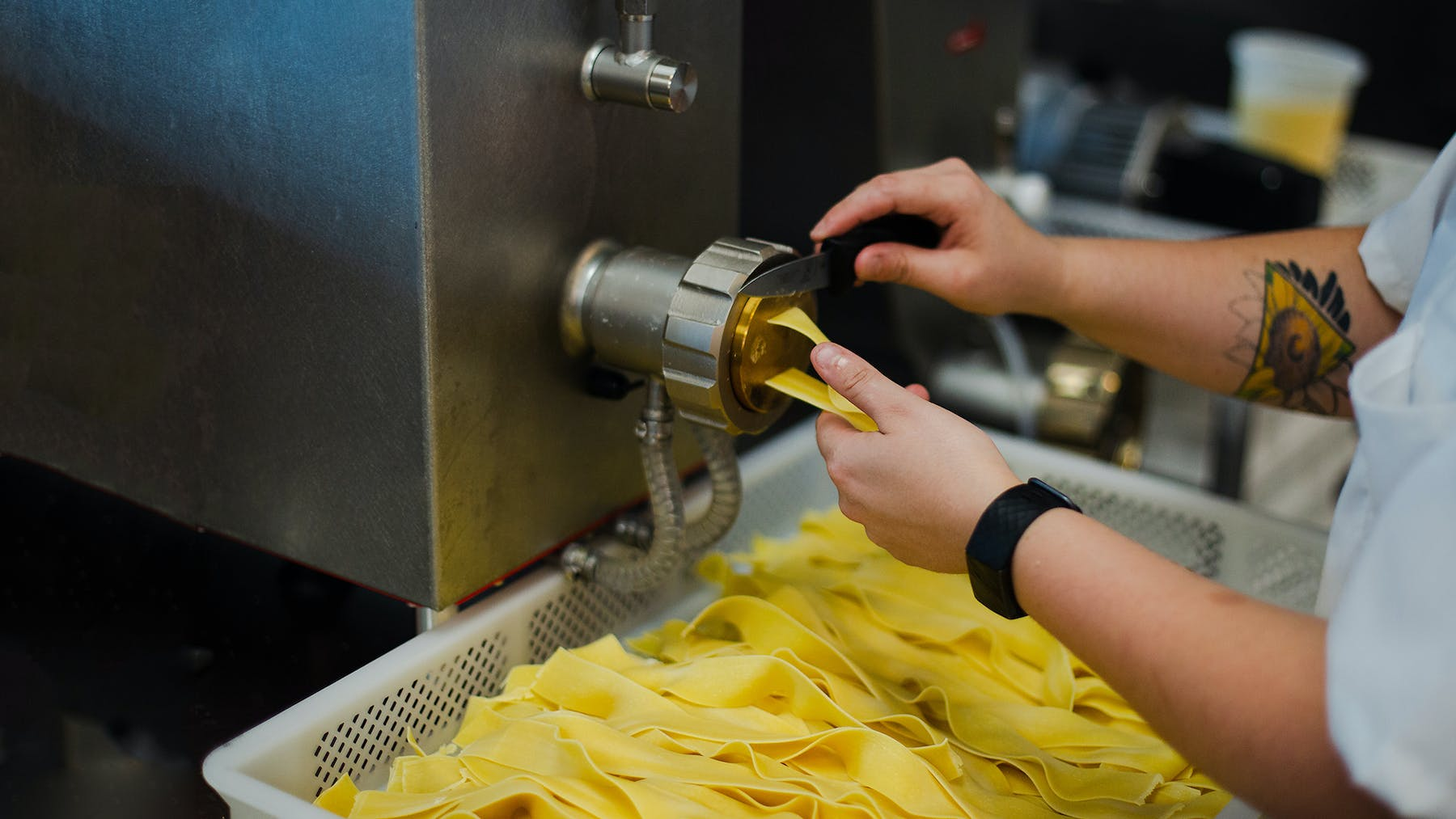 close up of hands making fresh pasta from an extruder