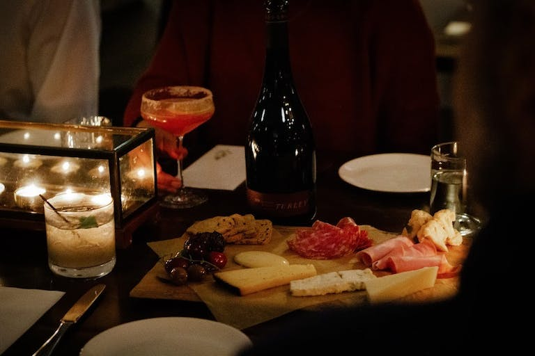 a bottle of wine on a table with a plate of food