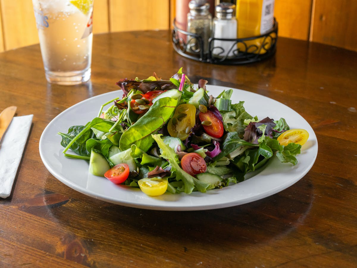 a plate of salad and a glass of beer on a table