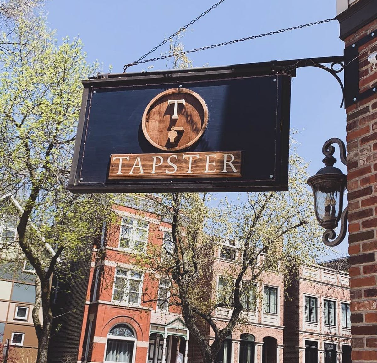 Tapster bar street sign hanging off the side of a building.