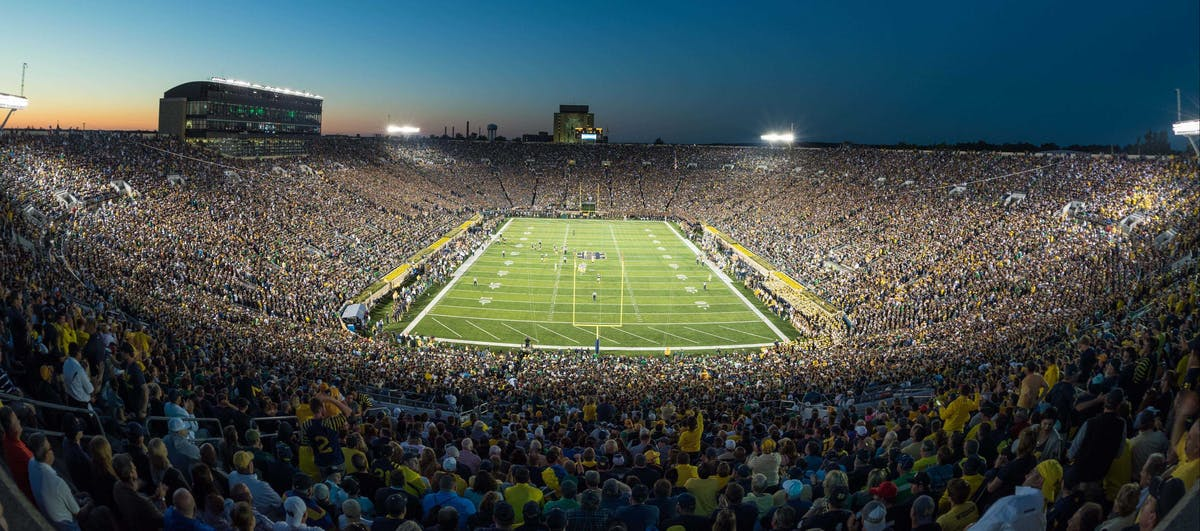 a stadium full of people with Michigan Stadium in the background