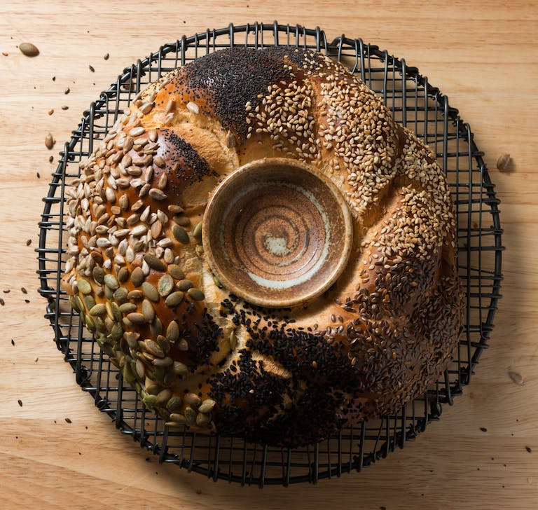 A round braided challah topped with seeds with a ceramic bowl in the center