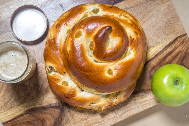 a spiral-shaped raisin challah sitting on top of a wooden cutting board
