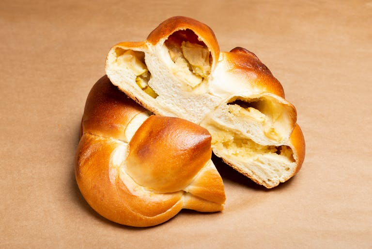 A round braided challah sliced in half to reveal its apple filling