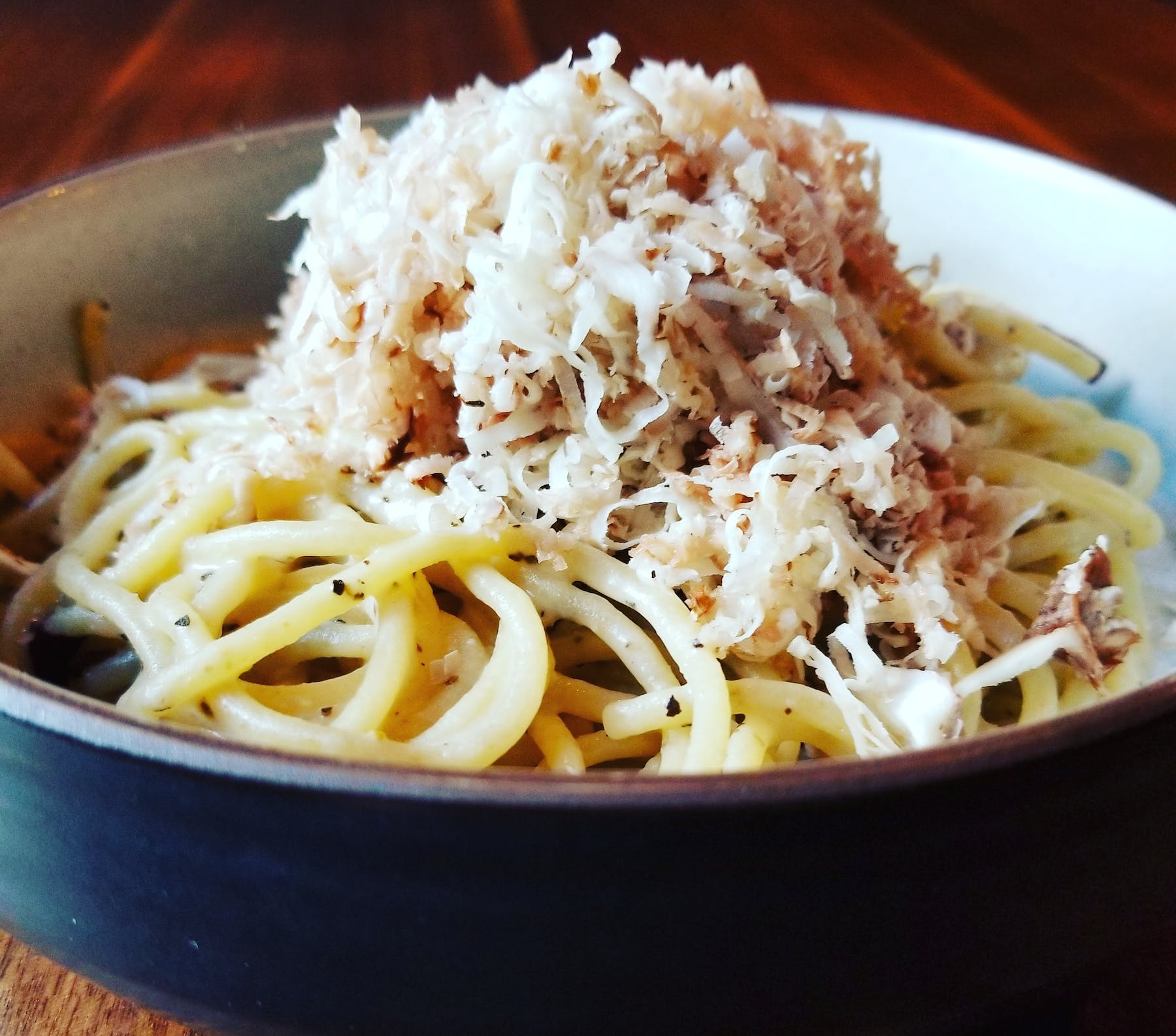 a bowl of pasta sits on a plate