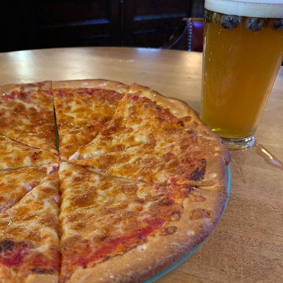 a pizza sitting on top of a glass of beer on a table
