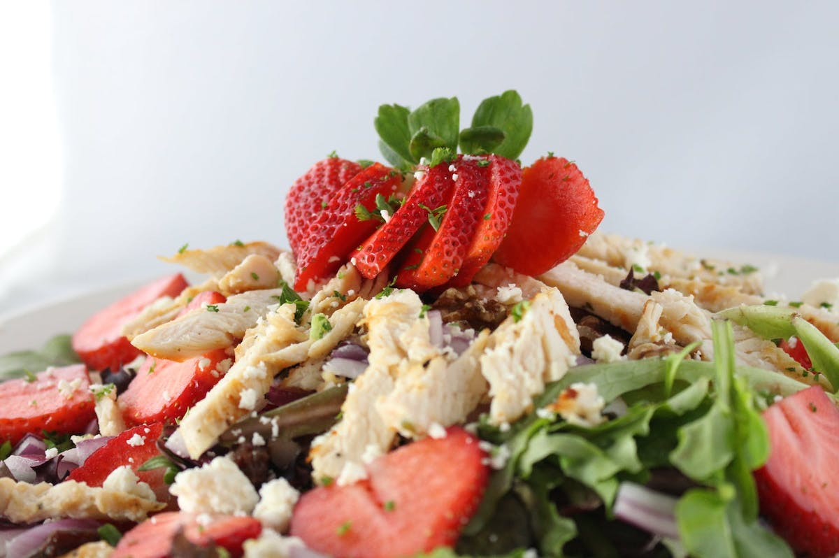 a dish is filled with salad topped with strawberry