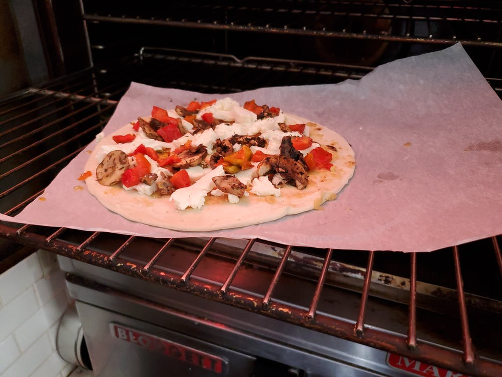 a pizza sitting on top of an oven