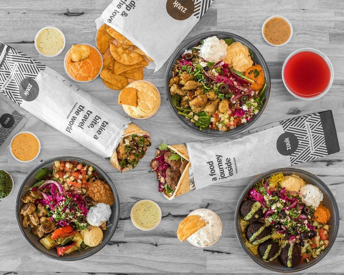 Zuuk Mediterranean Kitchen Spread With Bowls, Pitas, Salads, Pita Chips, Homemade Sauces