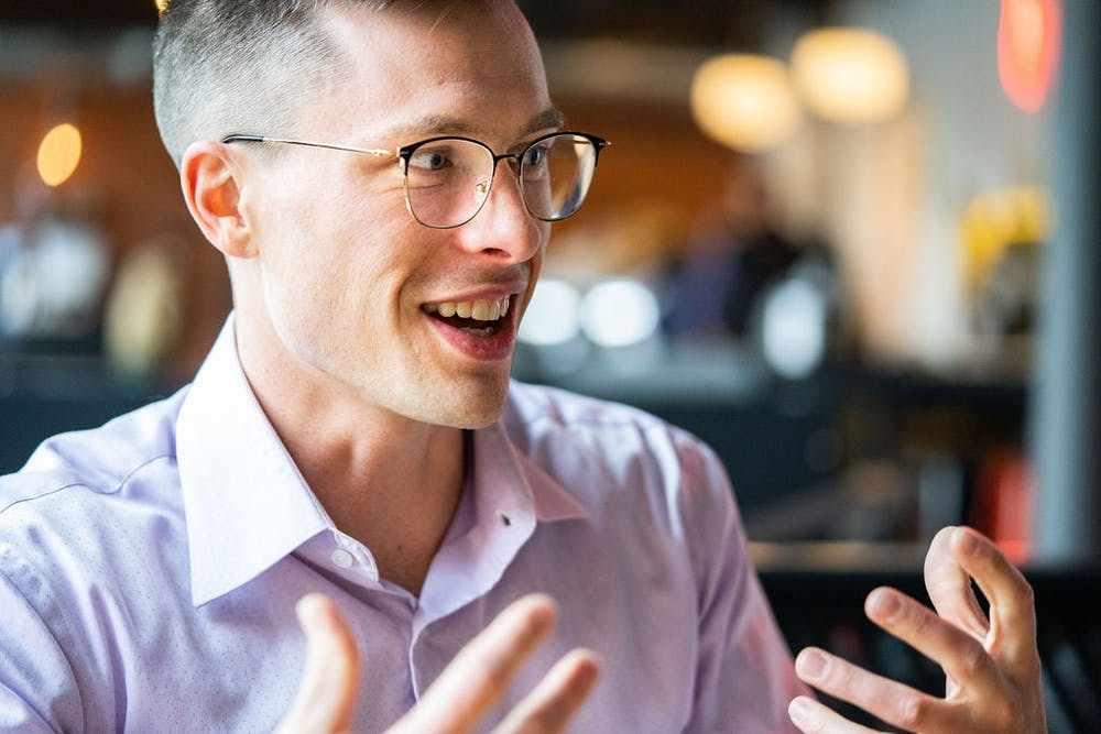 a man wearing glasses and smiling at the camera