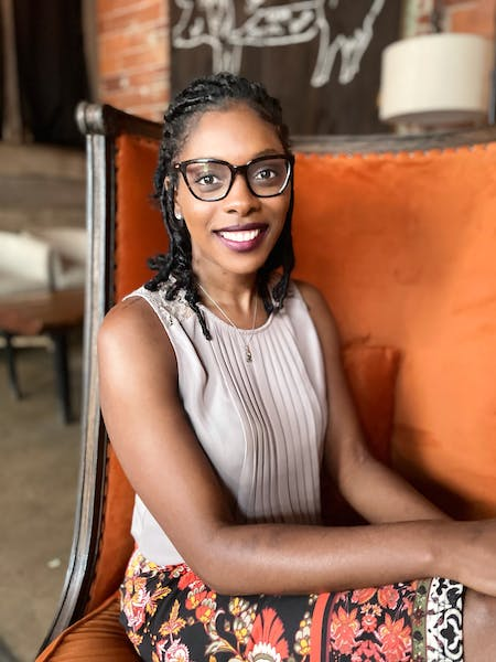 a woman in glasses looking at the camera