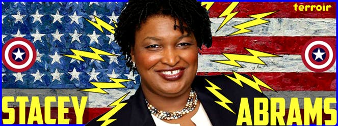 Stacey Abrams holding a sign posing for the camera