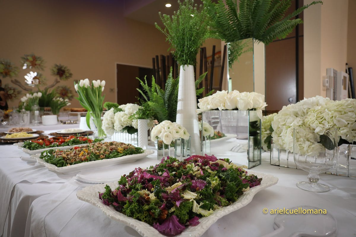 a white plate topped with a vase of flowers on a table