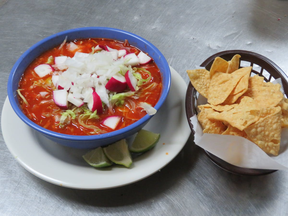 a bowl of food on a plate beside a nacho chips bowl