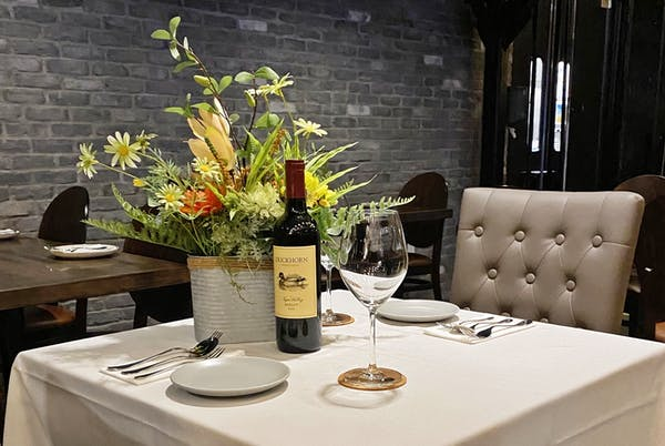 a vase of flowers on a table with wine glasses