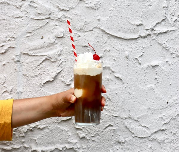 a hand holding a cold brew ice cream float