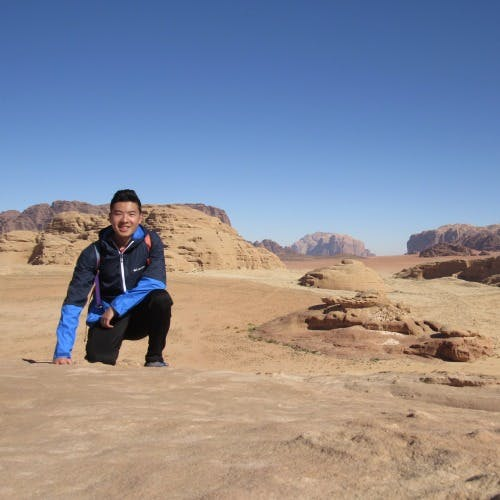 a man crouching in a desert for a picture