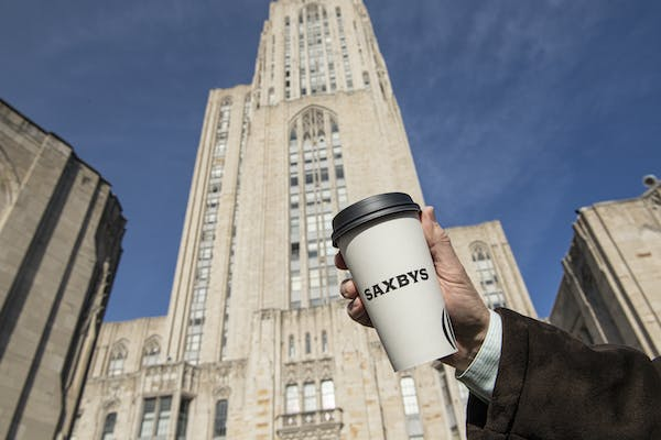 a person holding a saxbys cup in front of a tall building