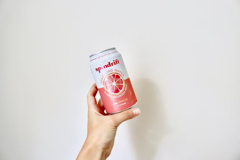 a hand holding a flavored sparkling water