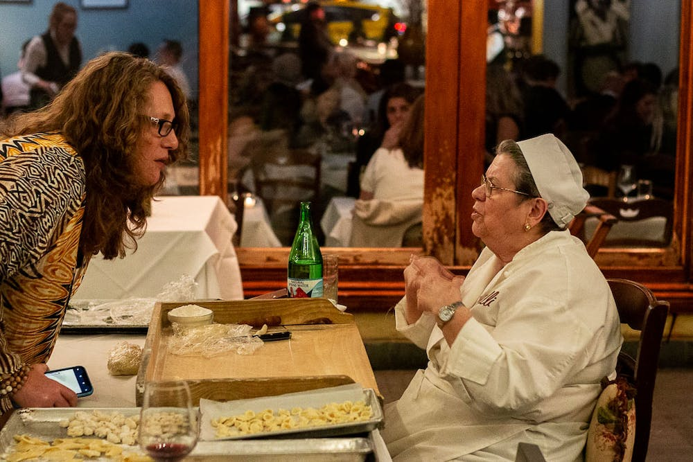 a woman sitting at the table talking to another woman. pasta is on the table between them.