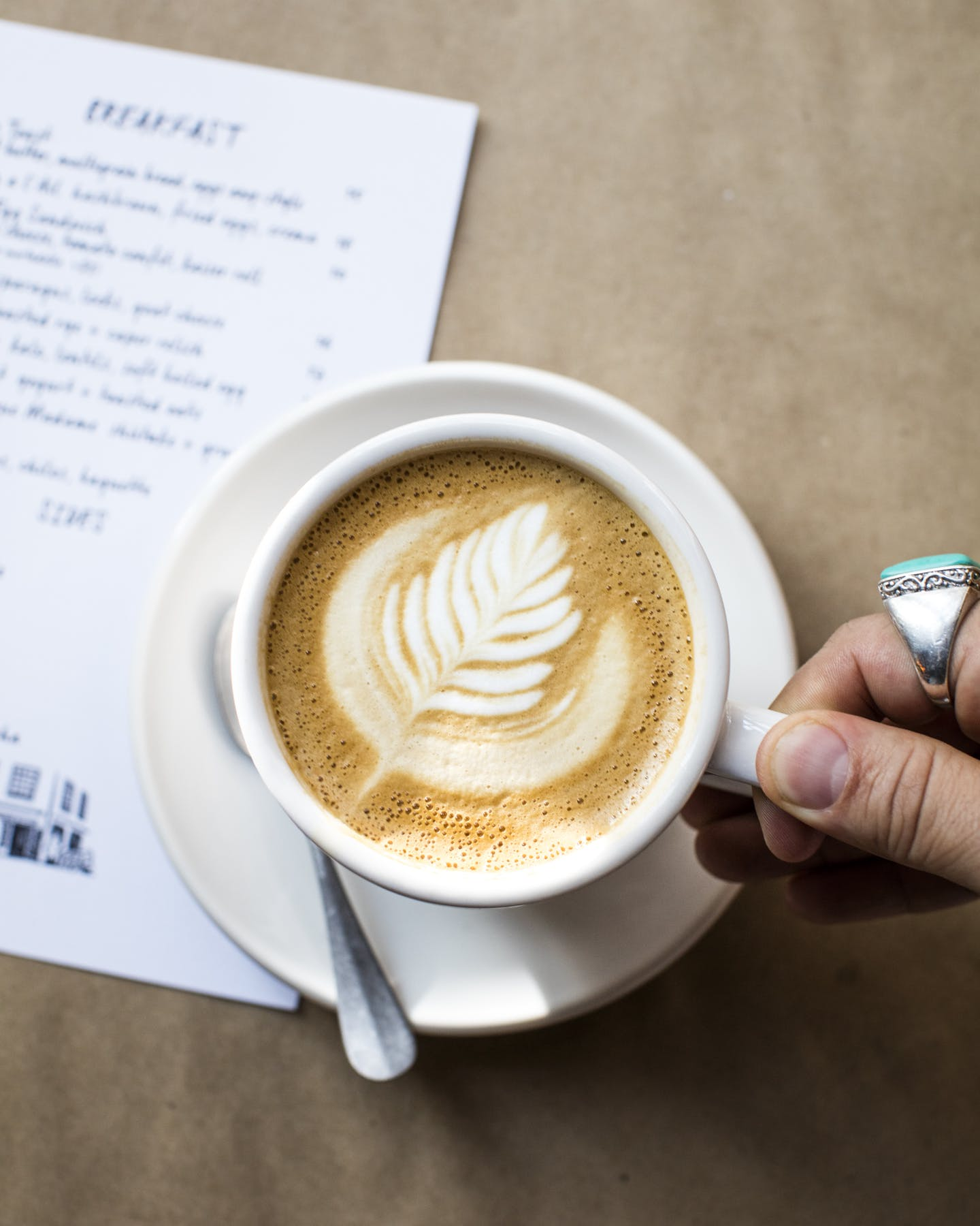 a hand holding a cup of coffee