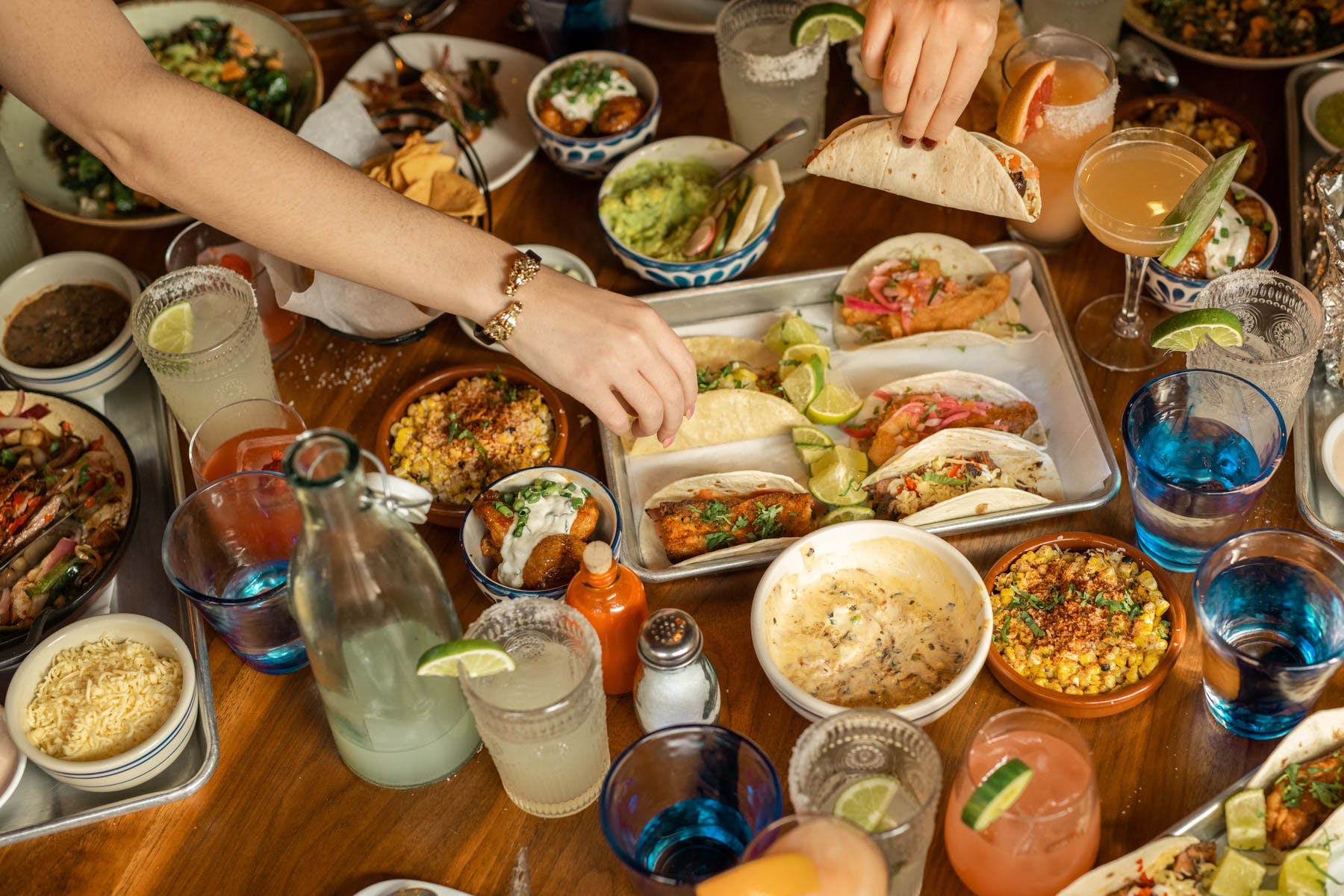 a group of people sitting at a table full of food
