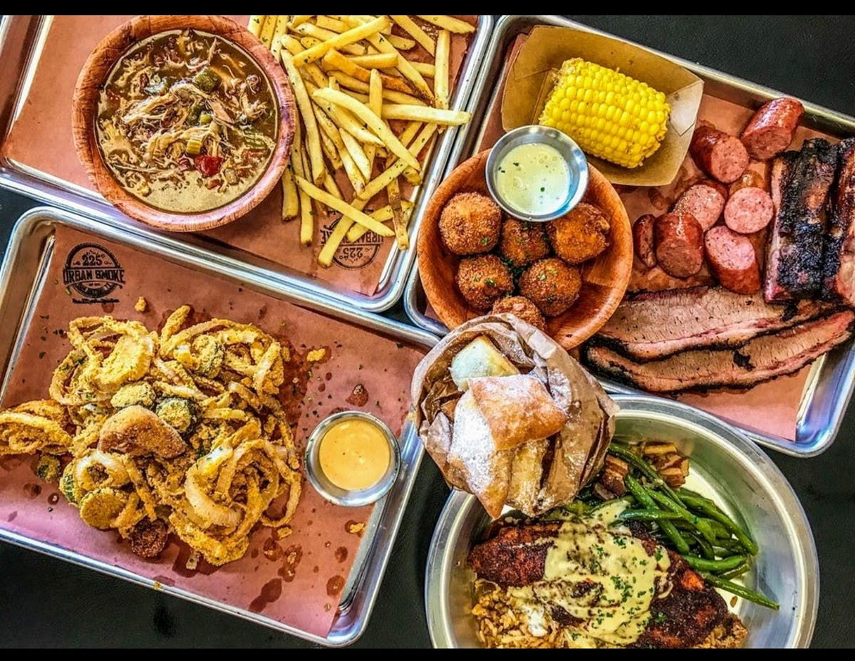 several trays of food on a table with many sauces