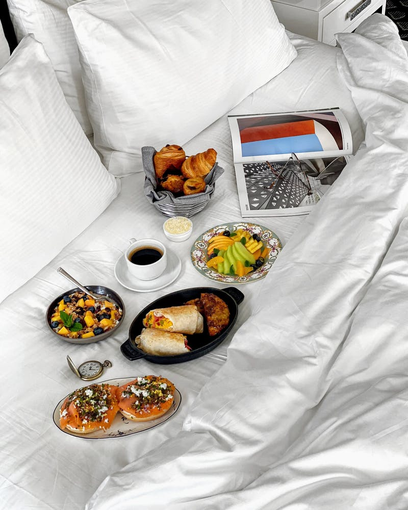 a table topped with plates of food on a bed