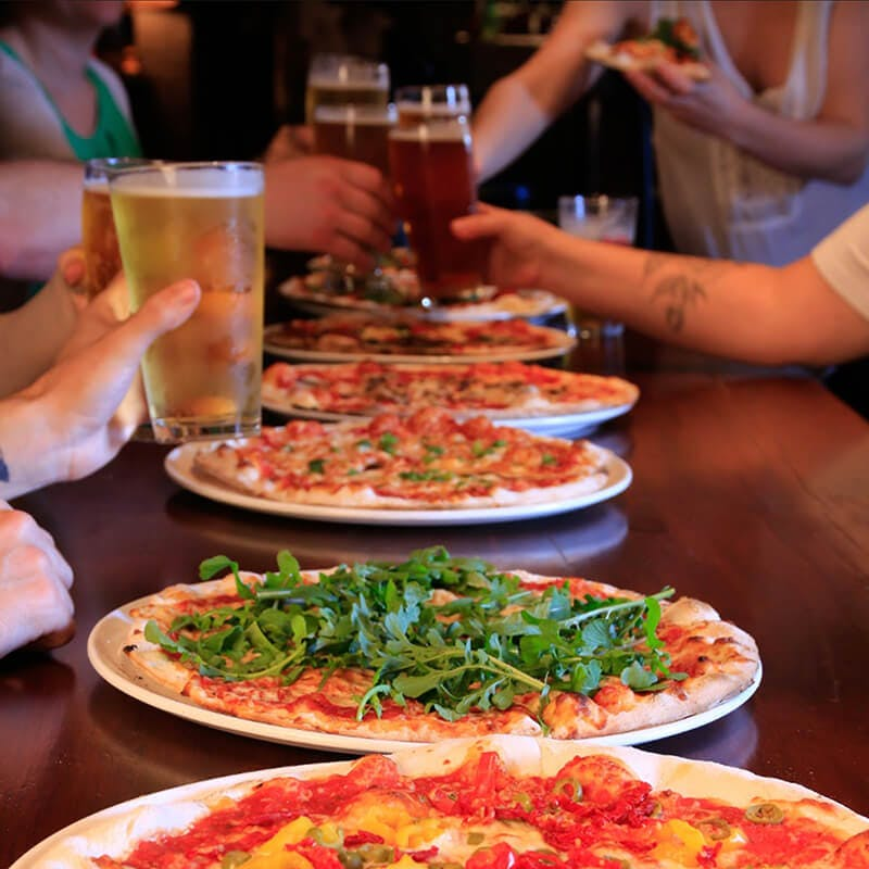a group of people sitting at a table with many plates of pizza