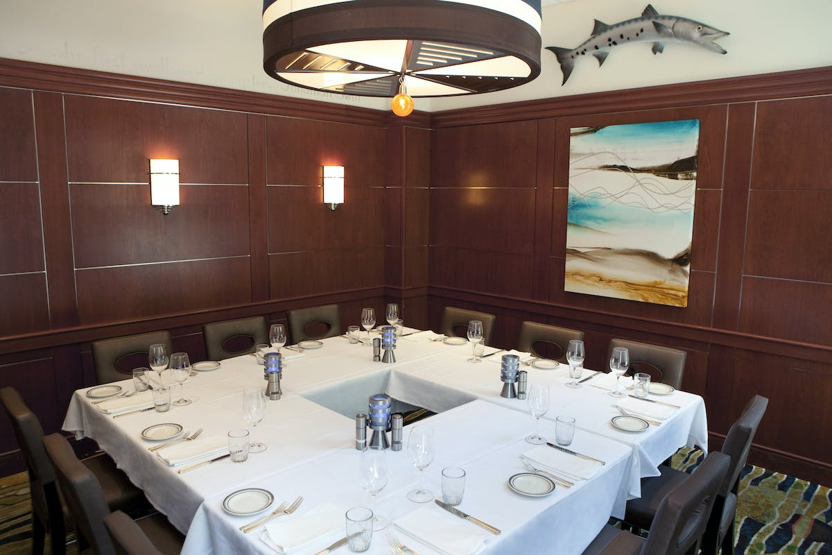 a room with a large table set with plates and wine glasses