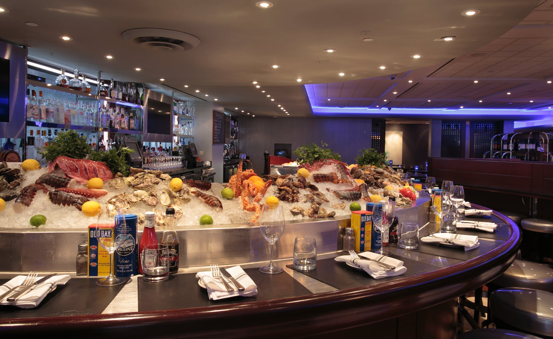 a dining room with a large pool filled with seafood and drinks