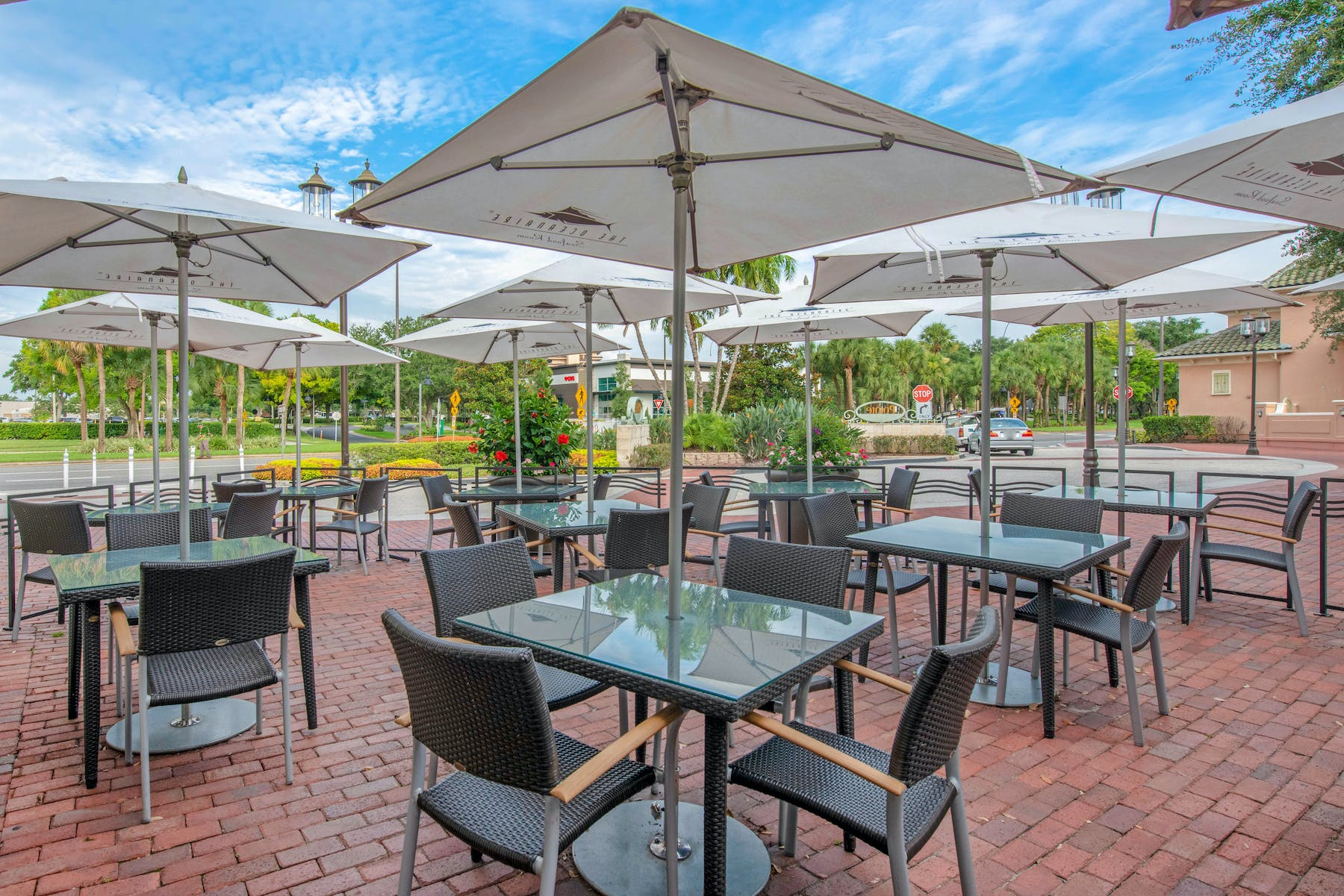 eating tables set with chairs and umbrellas outside