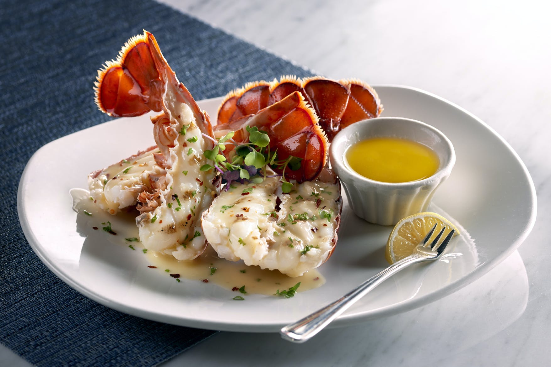 a plate of lobster with sauce on the side