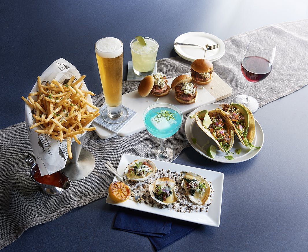 a table topped with plates of tacos, fries, hamburgers, beer and cocktails