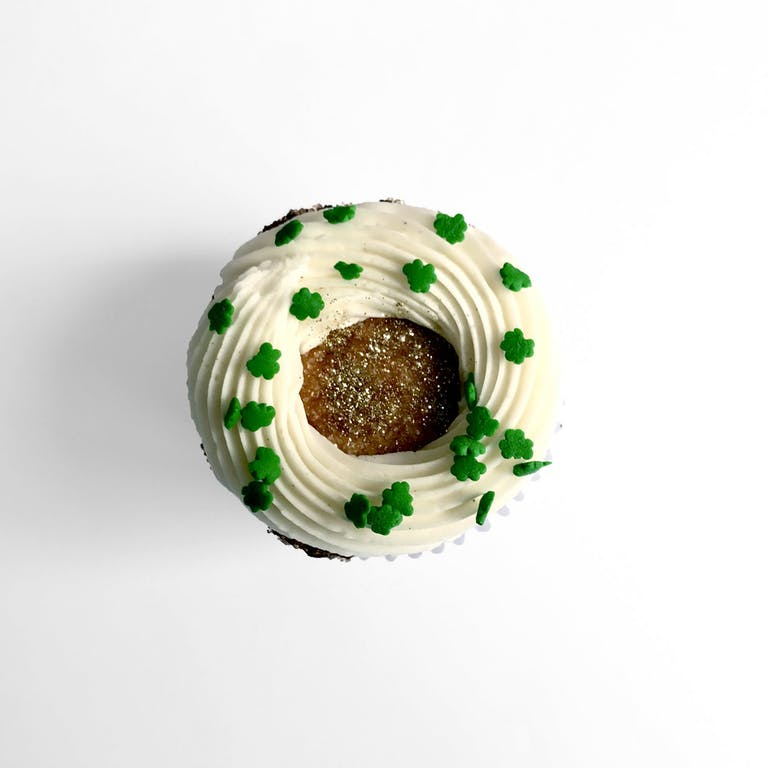 Chocolate cupcake filled with cream cheese frosting, mini chocolate chips, shamrock sprinkles & gold glitter