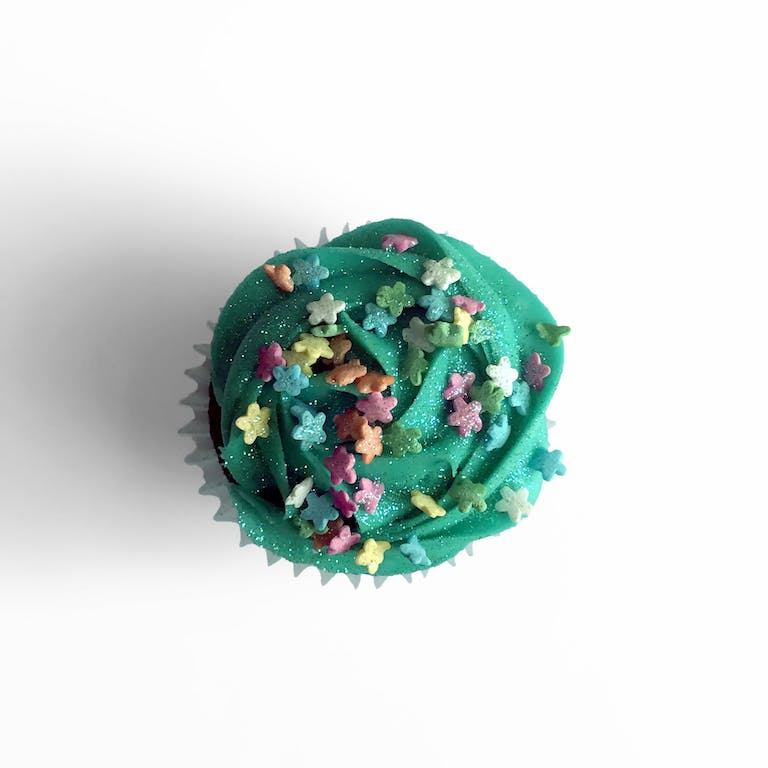 Chcocolate cupcakes filled with mini chocolate chip cream cheese frosting, topped with turquoise cream cheese frosting, daisy sprinkles and edible glitter