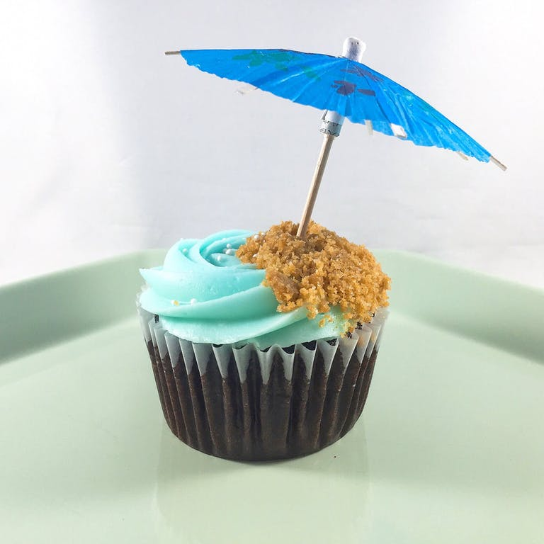 Chocolate cupcakes with a caramel filling, topped with ocean blue cream cheese frosting, graham cracker crumbles, seashore sprinkles and a mini beach umbrella