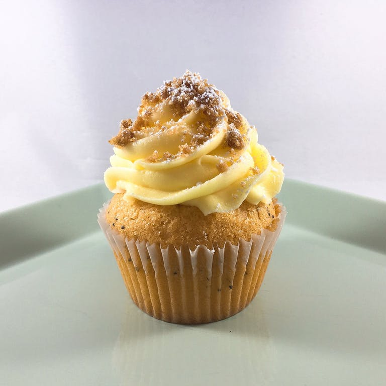 Lemon cupcakes with baked in graham cracker crumble and lemon curd filling, topped with lemon buttercream, graham cracker crumbs and powdered sugar