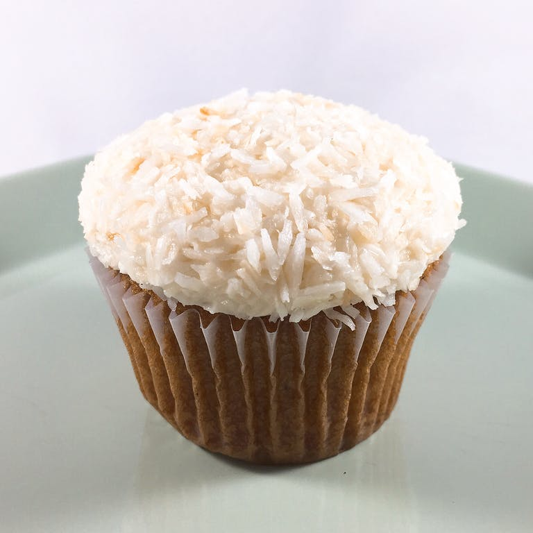 Vanilla cupcakes topped with vanilla buttercream dipped in toasted coconut flakes