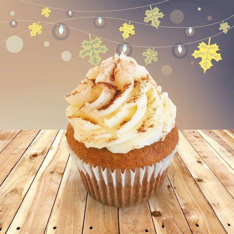 Pumpkin cupcakes filled with cream cheese frosting, topped with fresh whipped cream and pumpkin pie spices