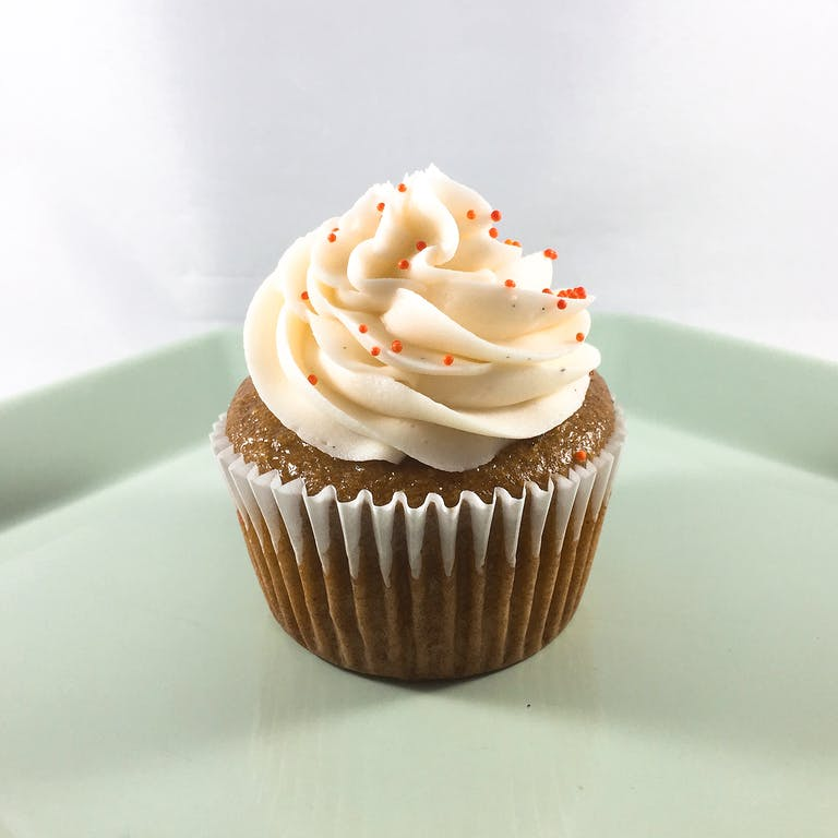 Sweet potato cupcakes filled with cream cheese frosting, topped with vanilla buttercream and orange nonpareil sprinkles