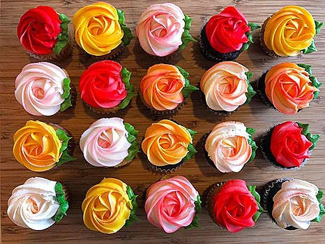 An assortment of vanilla and chocolate cupcakes topped with a rose buttercream design