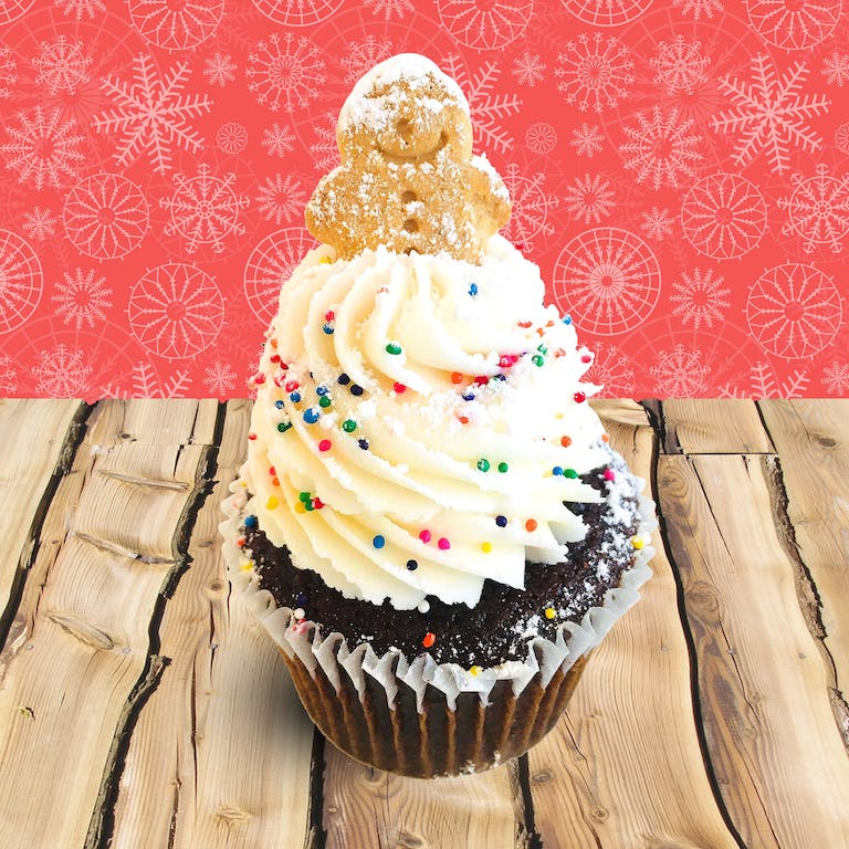 Gingerbread cupcakes filled with cream cheese frosting, topped with vanilla buttercream, rainbow nonpareil sprinkles, a dust of powdered sugar and a gingerbread man cookie