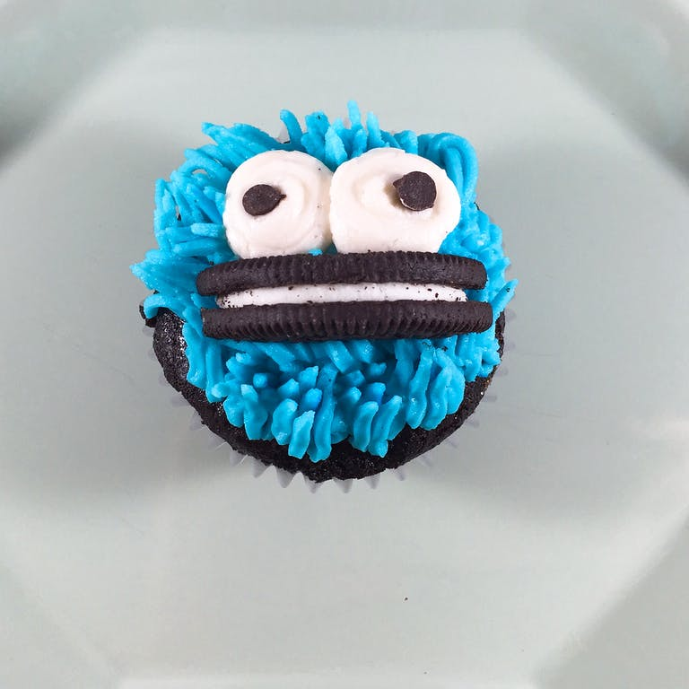 Vegan chocolate cupcakes with a vegan blue frosting Cookie Monster design and an Oreo cookie smile